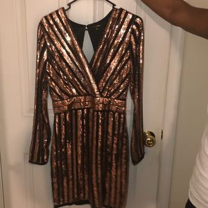 rose gold and black dress with a slit on the left.